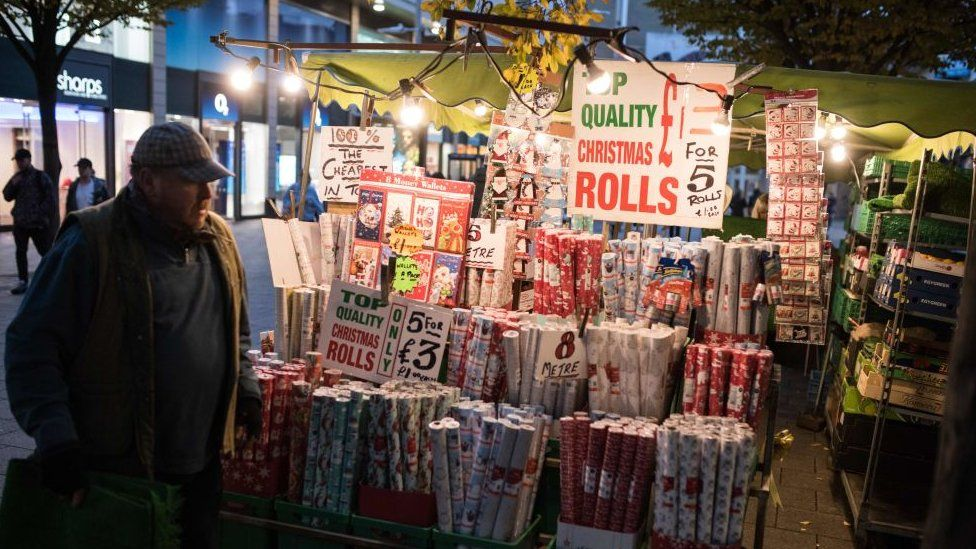 A man in a flat cap stands by a wrapping paper stall