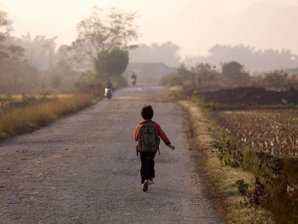 Young Boy Skipping Down A Road In China; Guangxi Zhuang,China