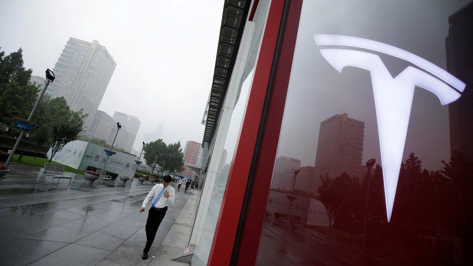 A man walks near a logo of Tesla outside its China headquarters in Beijing