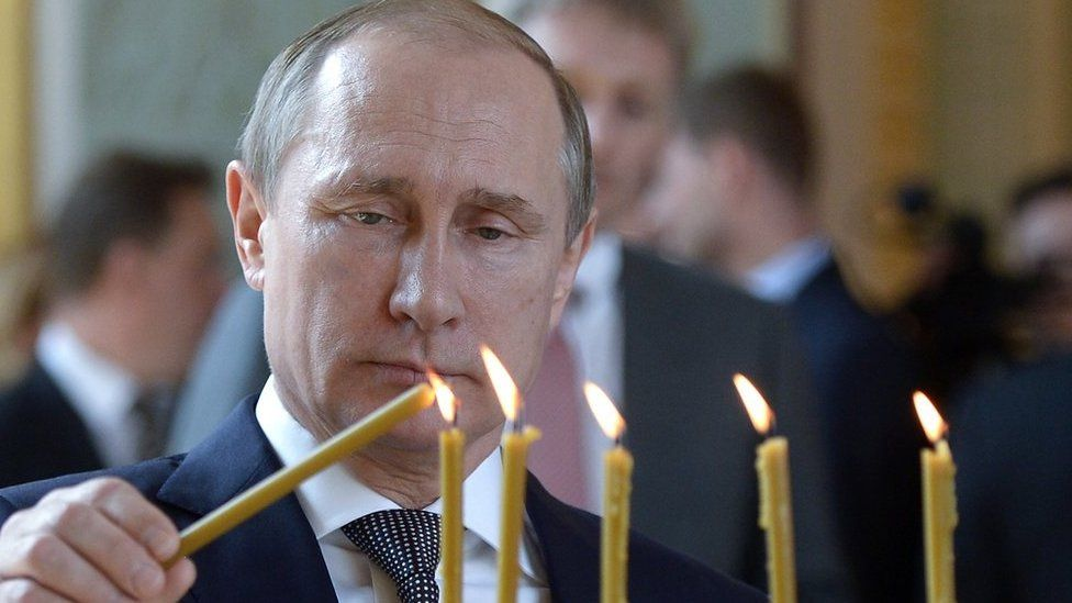 A picture of Vladimir Putin lighting candles