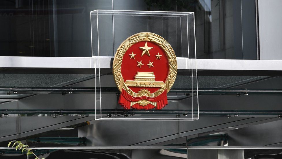 Police officers stand guard next to China's liaison office emblem being protected by plexiglass during a demonstration in Hong Kong on July 28, 2019.