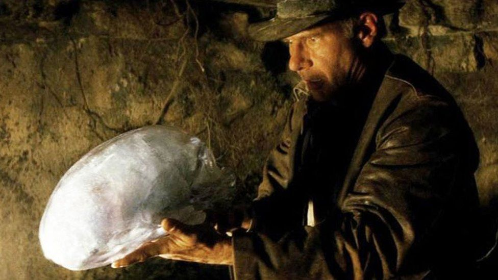 Indiana Jones (Harrison Ford) yn gafael yn un o'r penglogau mewn golygfa o'r ffilm.