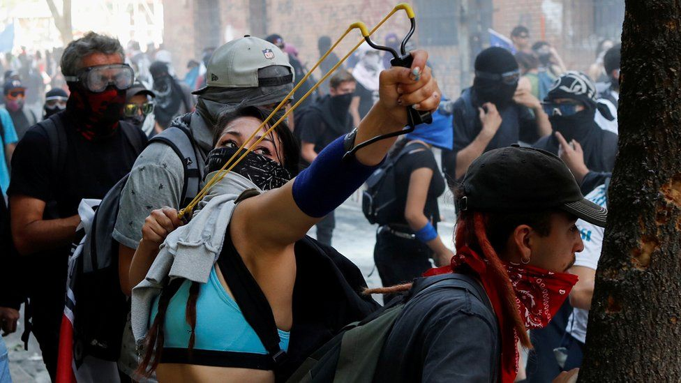 A woman holds a slingshot during a protest