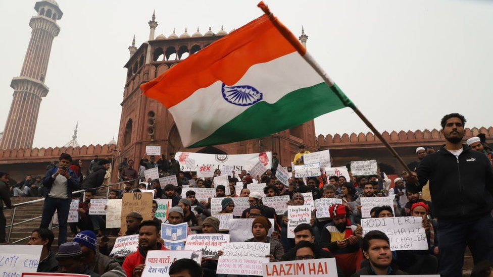 A student waves Indian flag during a sit in protest against the Citizenship Amendment Act (CAA) on the stairs of Jama Masjid in Old Delhi India on 19 December 2019