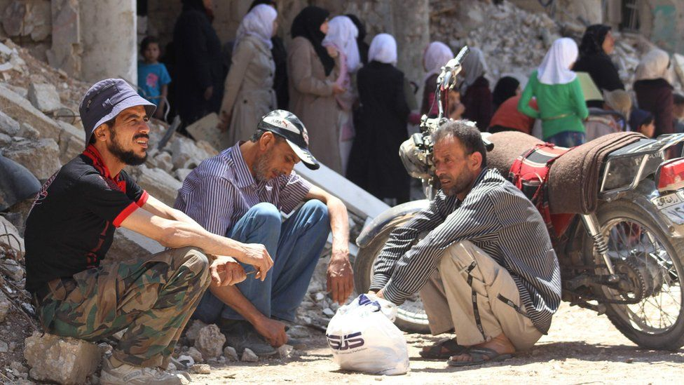 Syrian men sit next to a damaged building in the town of Daraya, southwest of central Damascus, on May 23, 2016