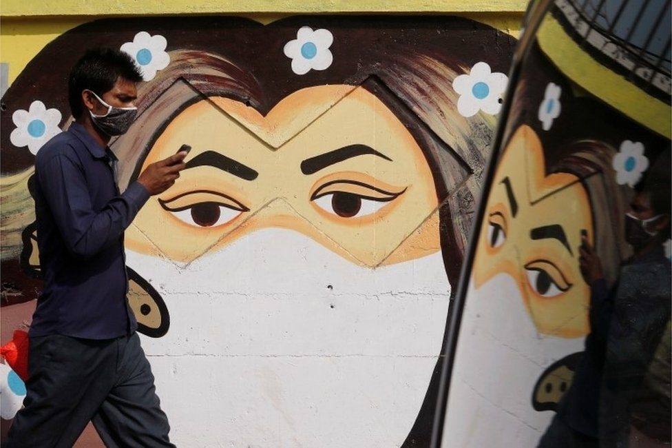 A man walks past a graffiti of a girl wearing a protective mask amidst the spread of the coronavirus disease (COVID-19) on a street in Navi Mumbai, India January 21, 2021.
