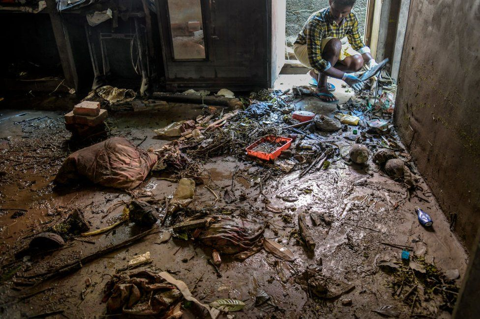 A man cleans up his house after returning home on 23 August as flood waters receded in Kerala.
