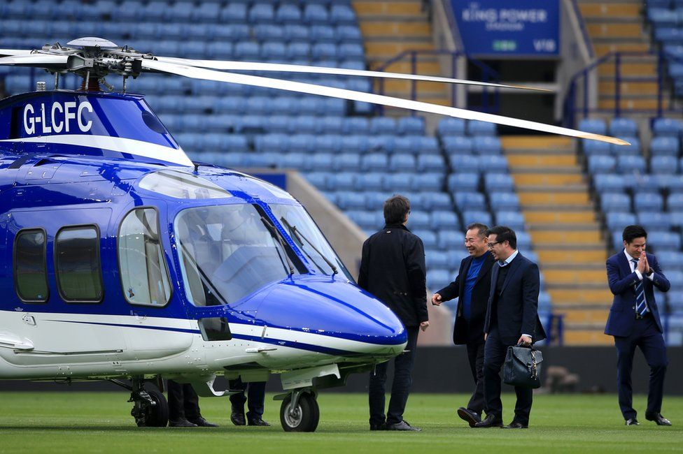 """Vichai Srivaddhanaprabha (second left) and vice chairman Khun Aiyawatt """"Top"""" Srivaddhanaprabha (second right) leave the ground in a helicopter after the final whistle in the Barclays Premier League match at the King Power Stadium, Leicester.. 03/04/2016"""