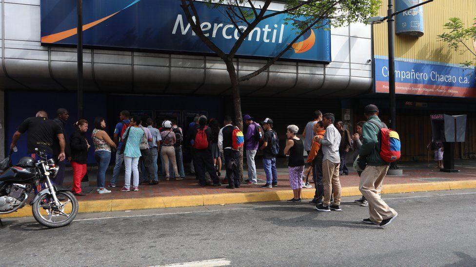People queuing outside a bank in Caracas, Venezuela