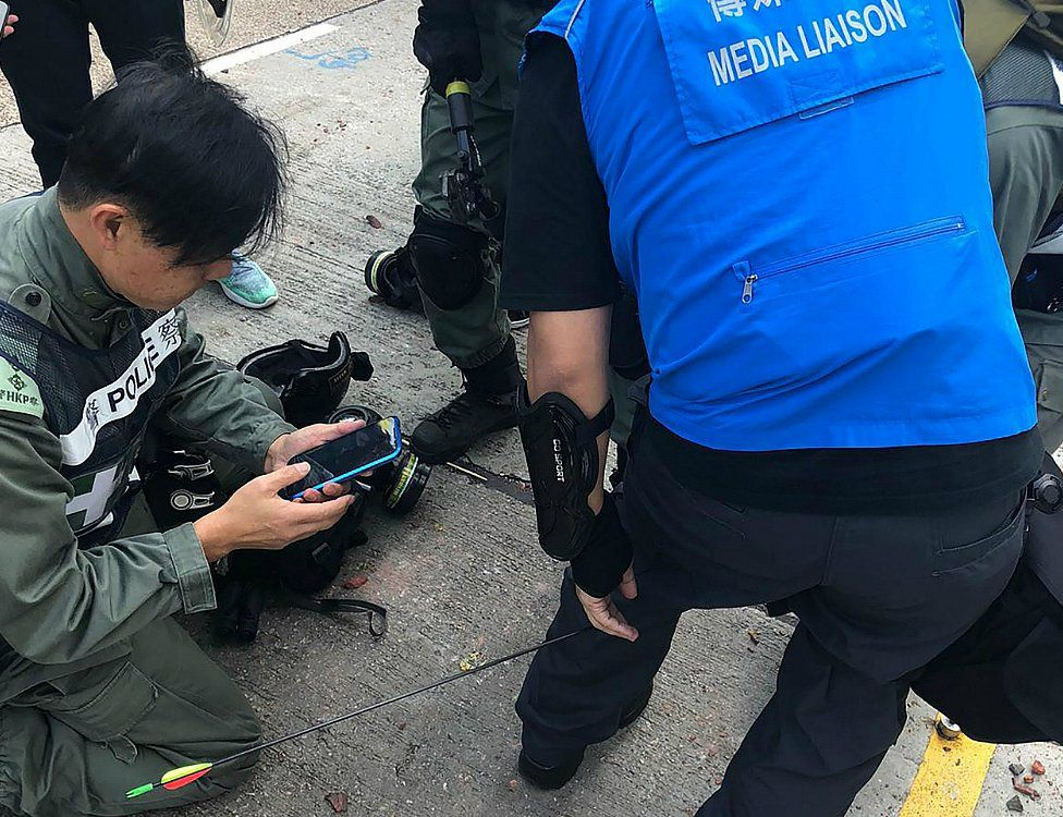 Police media liaison officer hit in the leg by an arrow fired by rioters outside the Polytechnic University of Hong Kong. 17 Nov 2019