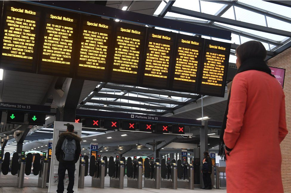 Commuters look on at blank departure boards