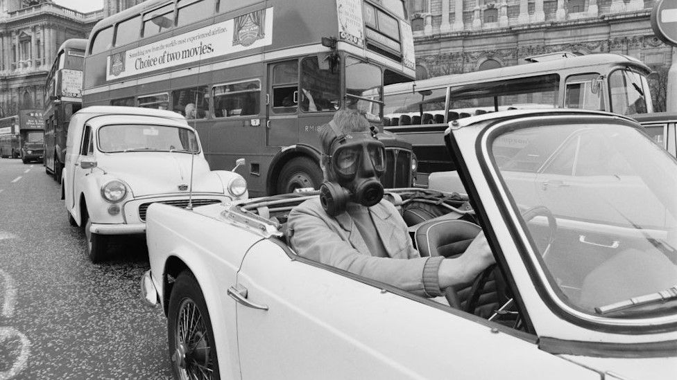 Driver wearing mask, 1970s
