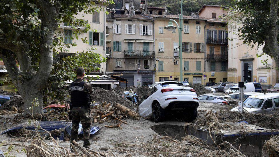 A gendarme stands amongst debris including vehicles in Breil-sur-Roya, south-eastern France