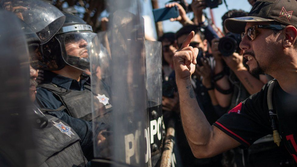 A demonstrator, part of a protest march against migrants, shouts towards a line of police in riot gear who were standing guard over a temporary shelter housing a caravan from Central America trying to reach the U.S., in Tijuana, Mexico