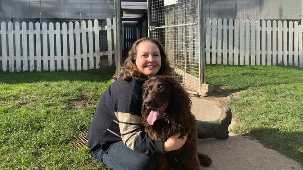 Andrea Burley and her dog Baxter in front of the kennel