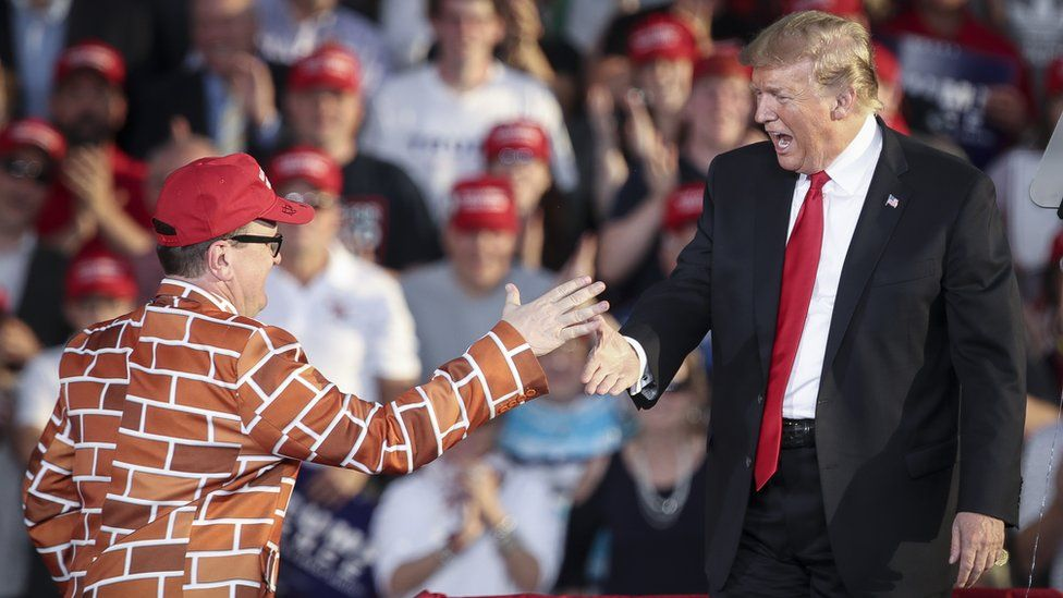 Trump greets a man dressed in a border wall suit during a rally
