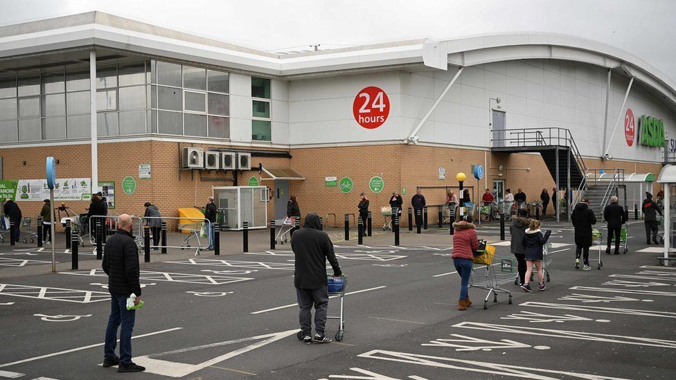 People queue for supermarket while social distancing