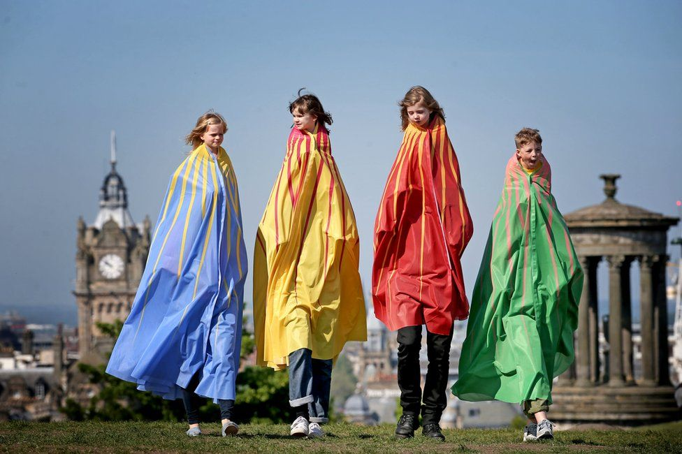 """Dressed in giant capes, children take part in """"The Tallest"""" one of over 100 pop-up performances featured in this year's Edinburgh International Children's Festival"""