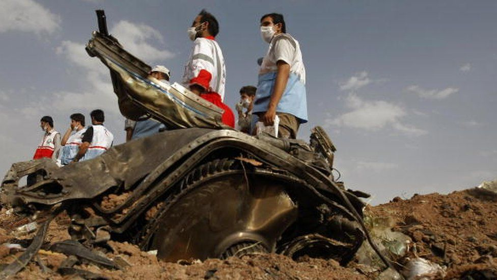 Members of Iran's Red Crescent stand near a piece of the Caspian Airlines Tupolev-154, which crashed near the city of Qazvin, north-west of Tehran (16 July 2009)