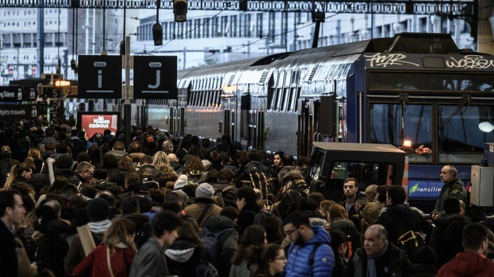 Travellers walk on a platform at the Gare de Lyon railway station in Paris on December 20, 2019
