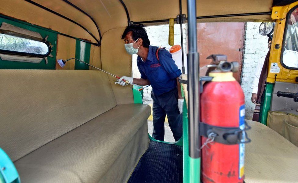 DTC cleaning staff chemically disinfect and sanitize auto rickshaw as a precautionary measure in view of coronavirus concerns, at Vasant Vihar Depot on March 17, 2020 in New Delhi, India.