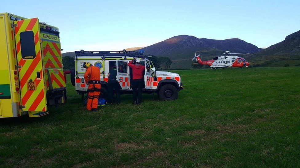 Members of the Mourne Mountain Rescue Team with an ambulance and an Irish Coast Guard helicopter