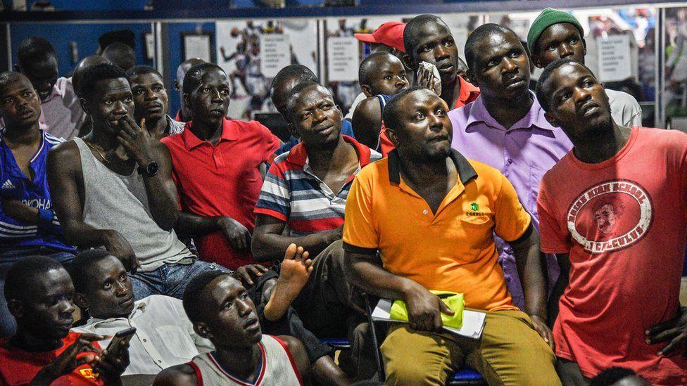 Men watching television in Ugandan betting shop