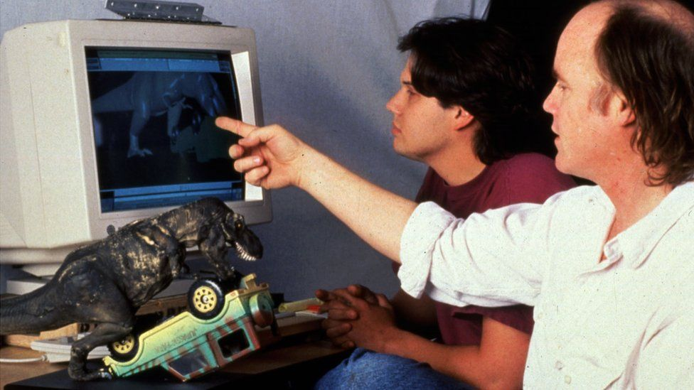 Two men look at a computer screen from the early 90s, with a computer animated dinosaur visible. A dinosaur model and jeep are on the desk beside them.