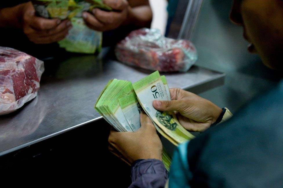 Shopper paying for meat with sheaf of banknotes