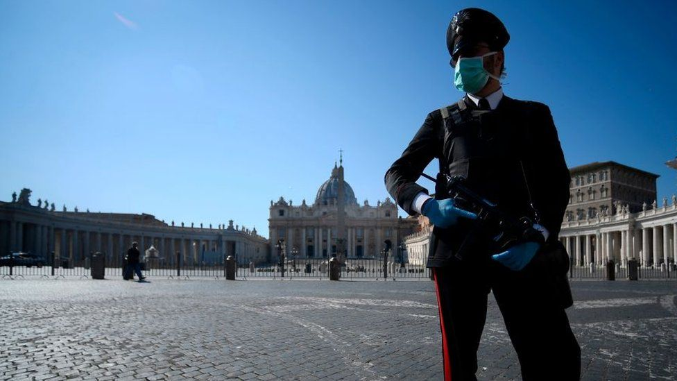 An armed police officer, wearing a face mask, patrols a closed and deserted St Peter's Square in the Vatican