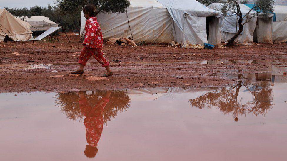 A girl walks through a flooded camp in north-western Syria
