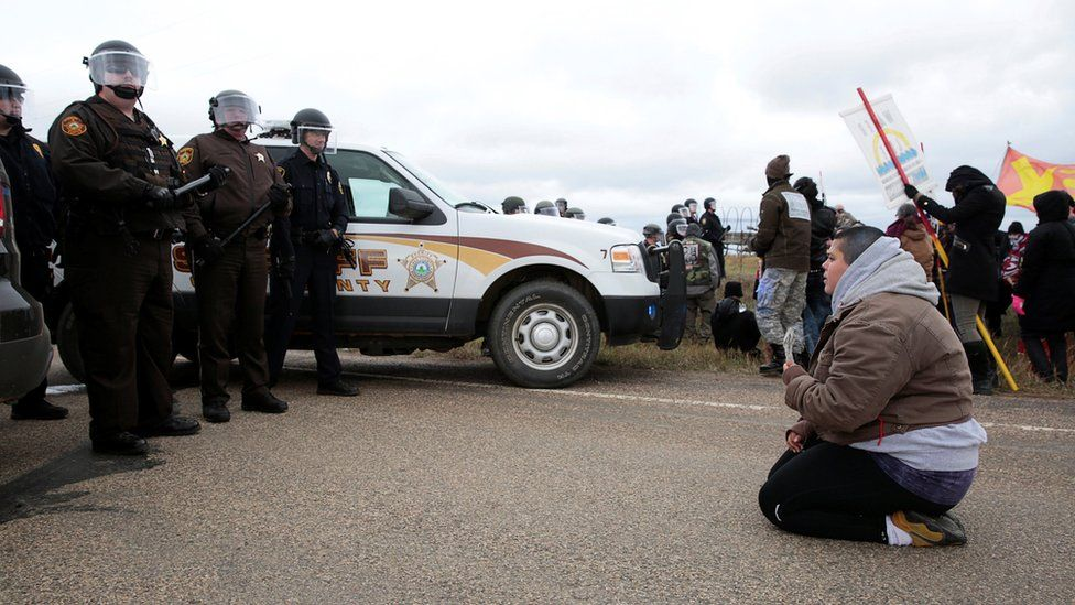 Caro Gonzales of Olympia, Washington, prays in front of police during a protest against the Dakota Access Pipeline between the Standing Rock Reservation and the pipeline route outside the little town of Saint Anthony, North Dakota, U.S., October 5, 2016.