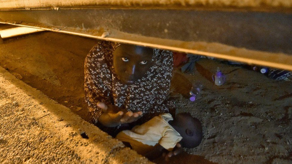 A migrant from Niger hides with her newborn child to avoid deportation at a transit centre in Tamanrasset in southern Algeria, 2 July 2018