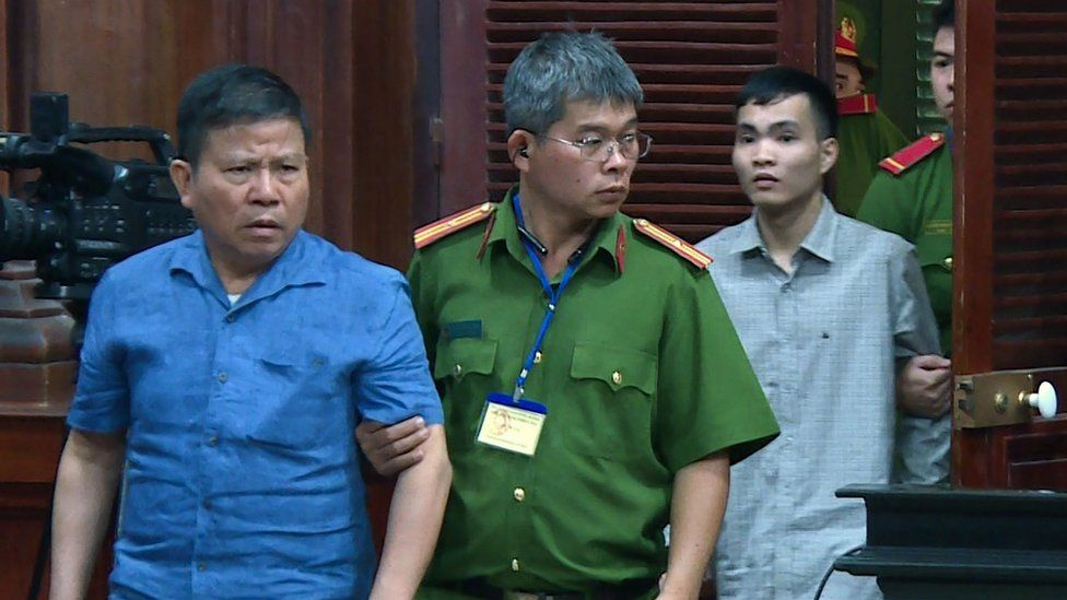 Chau Van Kham is escorted into court by police