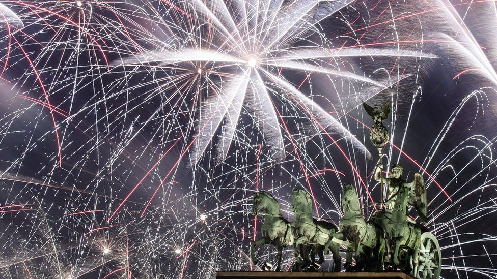Fireworks illuminate the sky over the Quadriga statue of the Brandenburg Gate during New Year's Eve celebrations in Berlin