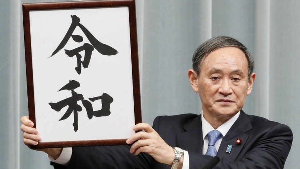 """Japan's Chief Cabinet Secretary Yoshihide Suga unveils the new era name """"Reiwa"""" at a news conference in Tokyo on 1 April, 2019"""