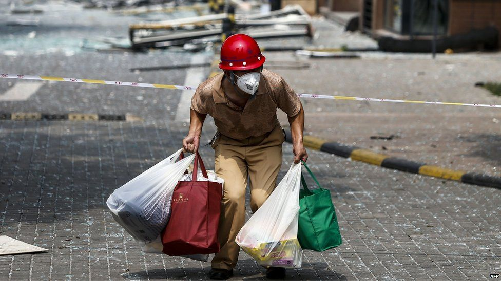 A victim of the explosions carrying his belongings walks out of his home in a residential area