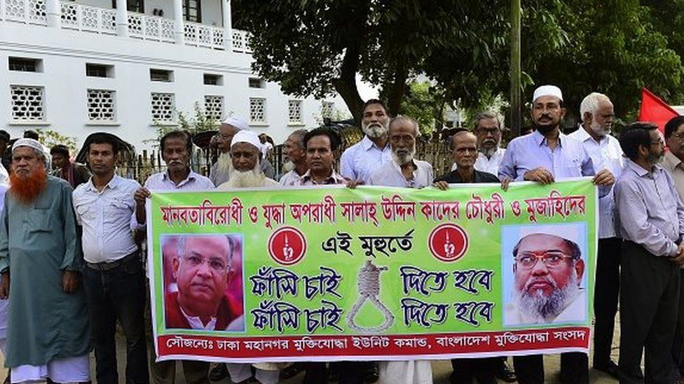 Bangladeshis who fought in the 1971 war of independence against Pakistan hold a banner calling for the execution of Salahuddin Quader Chowdhury (left) and Ali Ahsan Mohammad Mujahid (right) in November 2015