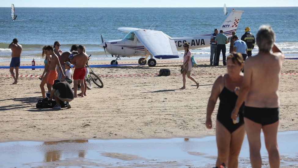 Onlookers watch the recovery of a light plane after two people were killed after the plane made an emergency on Sao Joao beach on Costa de Caparica in Almada, Portugal, 02 August 2017