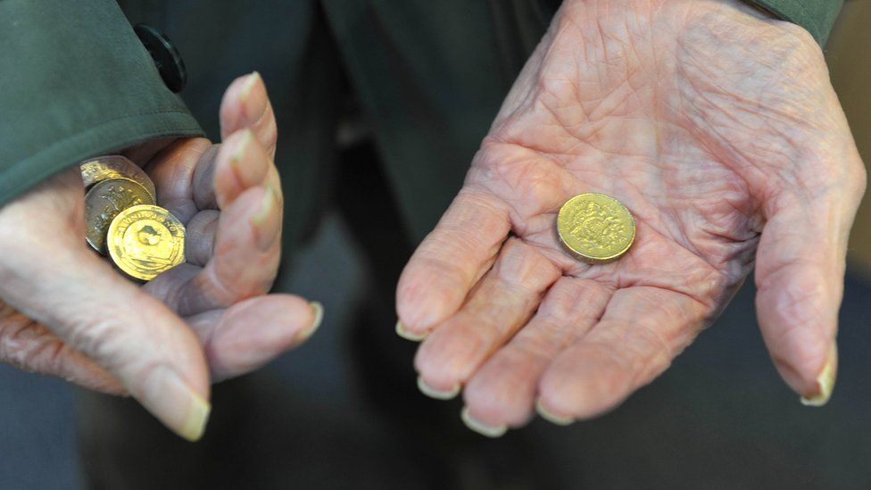 Elderly person's hands holding coins