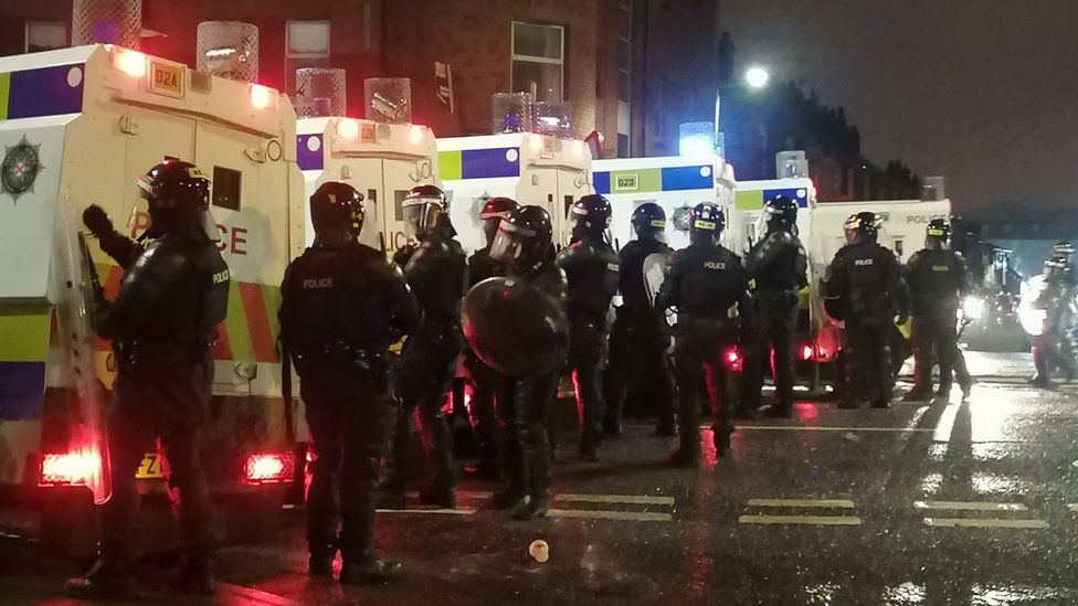 A line of police officers standing next to police jeeps on Wednesday night
