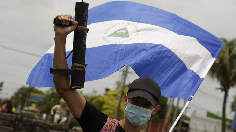 A young protester raises his artisan weapon and the Nicaraguan national flag, in Managua, Nicaragua, 15 June 2018.