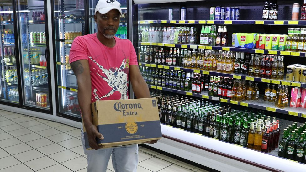 """A shopper carries a box of alcohol with the words """"Corona extra"""" ahead of a nationwide lockdown for 21 days to try to contain coronavirus in Johannesburg, South Africa"""