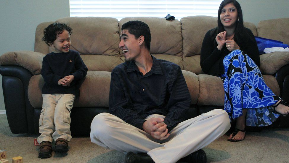 Jose Escobar, from El Salvador, shares a laugh with his son, Walter, next to his wife, Rose Marie Ascencio-Escobar, at their south Houston home on 27 January