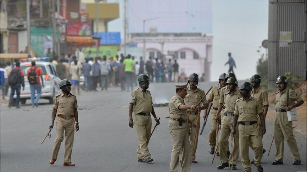 """Police personnel chase agitated pro-Karnataka activists as the Cauvery water dispute erupted into violence following the Supreme Court""""s order to release water to Tamil Nadu, in Bangalore on September 12, 2016."""