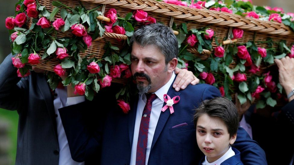 Andrew Roussos puts a hand around his son Xander as he carries his daughter's coffin