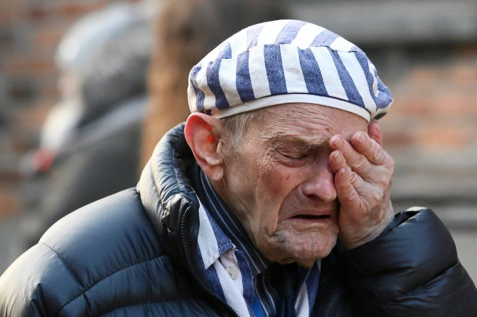 A survivor reacts at a Holocaust wreath-laying ceremony