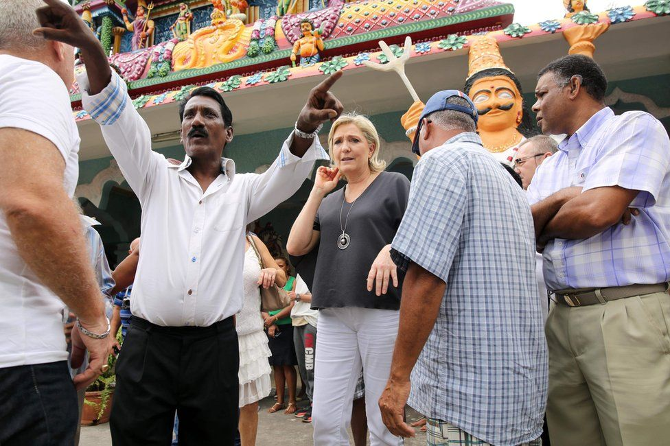 Marine Le Pen (C) visits a Hindu temple in Saint-Louis, on the Indian Ocean island of La Reunion, 27 November
