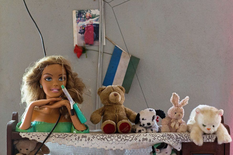 Dolls and cuddly toys lined up on a table