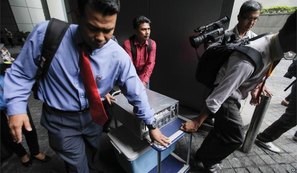 Malaysian plainclothes police carry a computer from the 1MDB (1 Malaysia Development Berhad) office after a raid in Kuala Lumpur, Malaysia, 8 July 2015